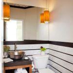 Powder Room With Wooden Floor, White Toilet, White Striped Wall, Brown Wooden Cabinet With Dark Brown Top Under Metallic Sink