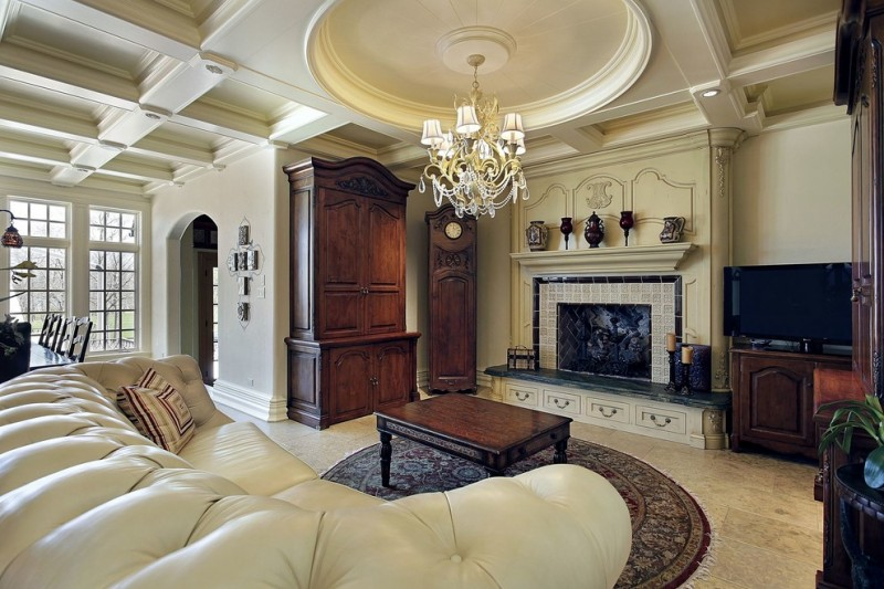 round area rugs for living room beige tufted leathered couch fireplace mantel black coffee table chandelier cabinet drawers