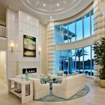 Round Area Rugs For Living Room White Sofas White Chairs Glass Coffee Table Fireplace Wall Sconces Glass Windows Curtains Artwork Beige Floor Tile