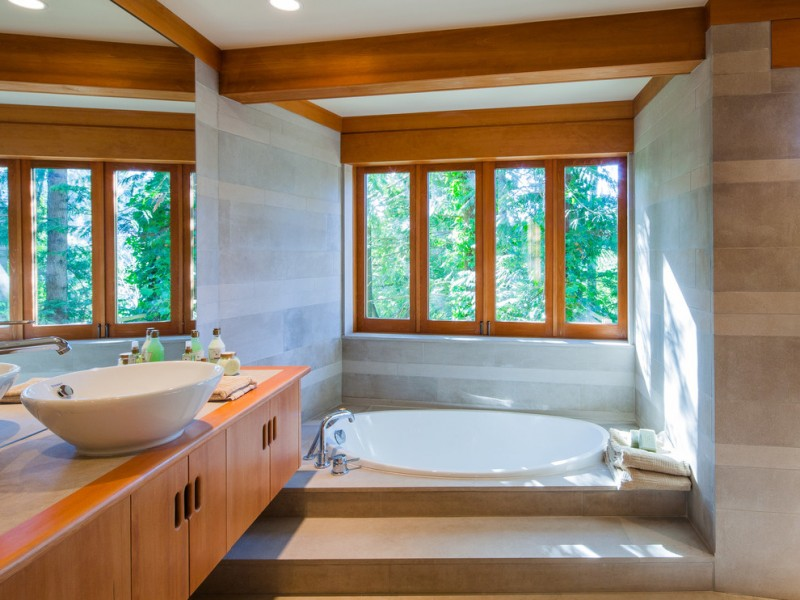 rustic bathroom with nude marble floor, white marble wall, brown wooden cabinet with brown wooden top and white sink, round sunken tab near glass window