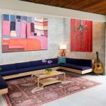 Rustic Modern Coffee Table Colorful Artworks Concrete Walls Patterned Rug Wooden Couch With Dark Blue Cushions Table Lamps Sliding Glass Door
