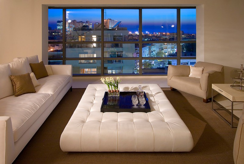 short couch white tufted ottoman black tray glass vase brown throw pillows beige armchairs side table grid windows brown area rug