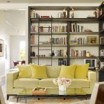 Short Couch Yellow Couch Yellow Throw Pillows Patterned Area Rug Tufted Chairs Wooden Side Table Glass Coffee Table Bookshelves