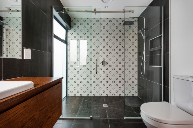 sliding shower head black wall and floor tiles wooden floating vanity white undermount sink mirror frosted glass windows sliding glass shower doors