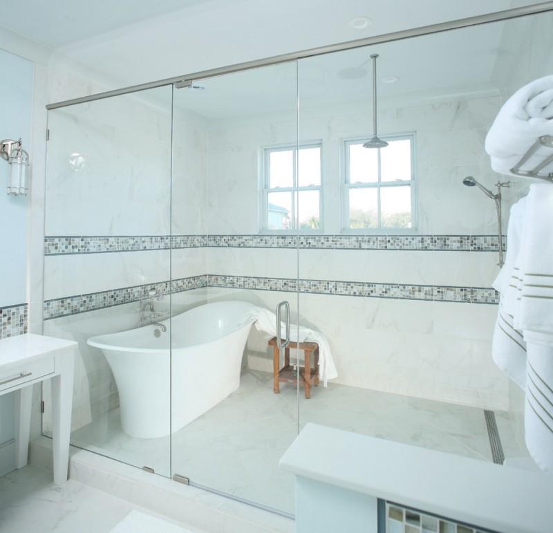 sliding shower head freestanding bathtub wooden bench long head shower window wall sconce towels tub filler towel holder