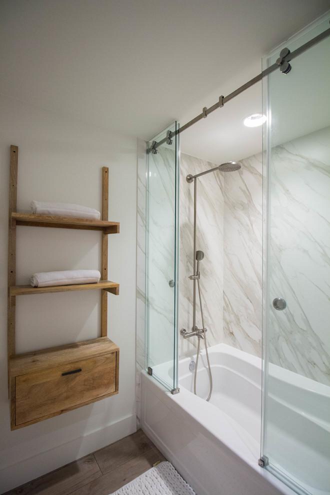 sliding shower head recessed lighting marble wall built in tub shower tub combo sliding glass shower door wooden shelf towels wooden floor bathroom mat