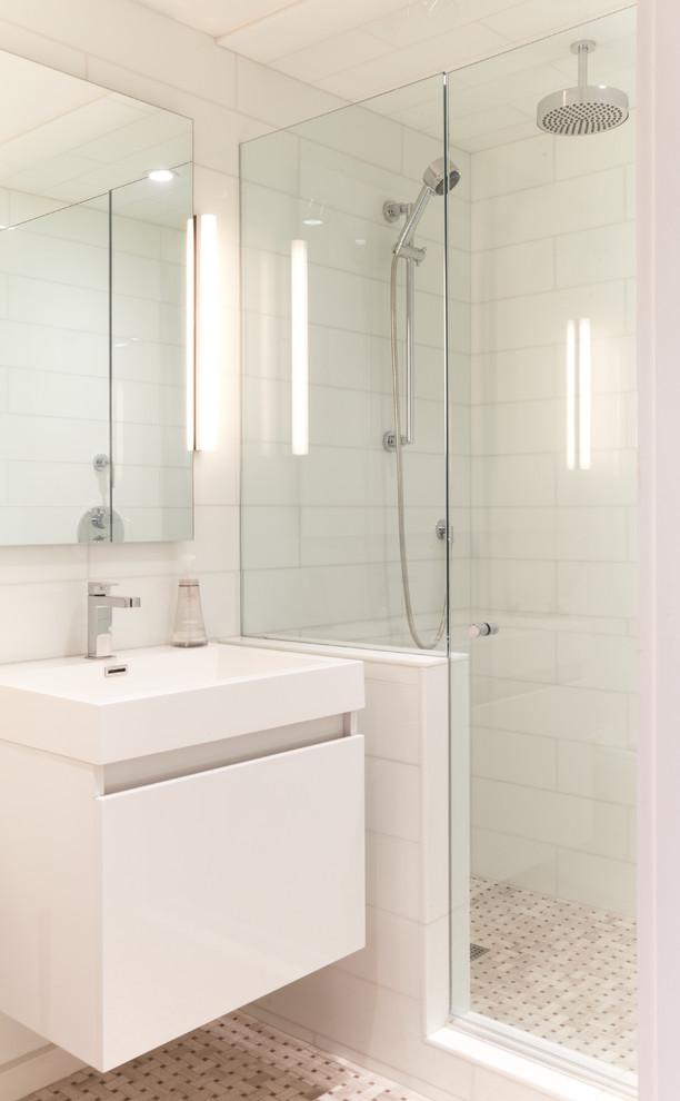 sliding shower head white floating vanity white undermount sink white wall tile beige mosaic floor glass door rainfall shower mirror wall sconce