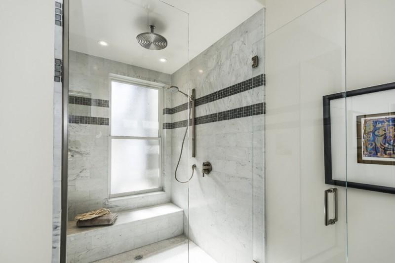 sliding shower head white marble wall tile black mosaic tile rainfall shower glass shower door built in bench frosted glass windows artwork