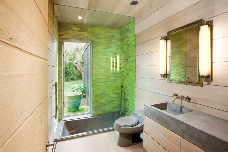small contemporary with brown nudish colored floor, light brown wooden cabinet with grey stone top, mirror, grey square sunken tub with green marble wall