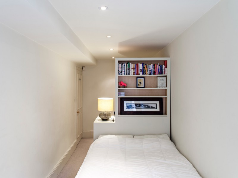 small narrow bedroom with white wall, white shelves and table, light brown floor