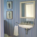 Small Toilet With Brown Tiles Floor, White Toilet, White Towel, White Square Framed Mirror, White Sink, White Wall Lamp, Blue White Striped Wallpaper