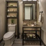 Small Toilet With Nude Wall And Floor, With Wooden Shelves, Metallic Sink, Metallic Framed Mirrors With Lamps On Top