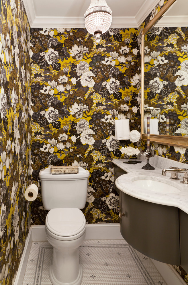 small toilet with white tilse floor, grey cabinet with white marble top and sink, large mirror, brown flowery wallpaper