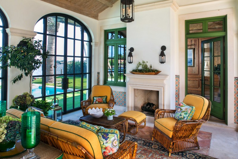 sunroom with turkish rug, rattan chairs and bench with orange cushion, rattan coffee table, fireplace, green framed door and windows, lamps on wall and ceiling