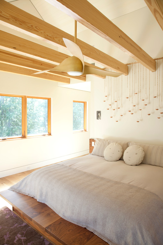 unusual ceiling fans with light wooden beams wooden platform bed grey bedding pillows wall decorations windows area rug wooden floor white walls