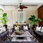 Unusual Ceiling Fans Wooden And Iron Coffee Table Rattan Sofas Geometric Area Rug Side Tables Windows Armchairs Throw Pillows Wall Sconce
