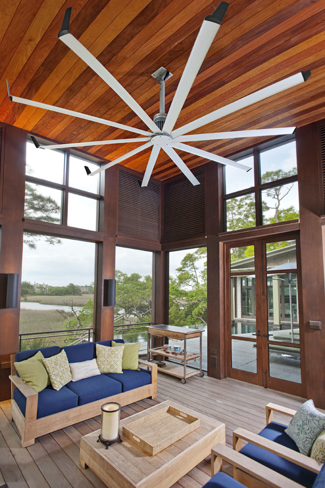 unusual ceiling fans wooden sofa black cushions throw pillows wooden coffee table wooden tray wooden armchairs glass windows glass doors