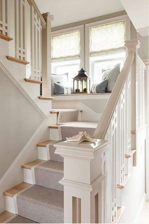 white and brown stairs with rug, seating in window sill