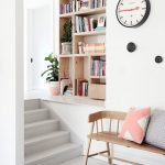 White Floor White Wall With Simple Clock, Wooden Bench With Pillows, White Short Stairs, Light Brown Shelves On The Crook