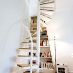 White Metal Spiral Stairs With Wooden Path, White Metallic Handrails In Small Places With White Wall, Brown Rug, And Built In Bookshelves