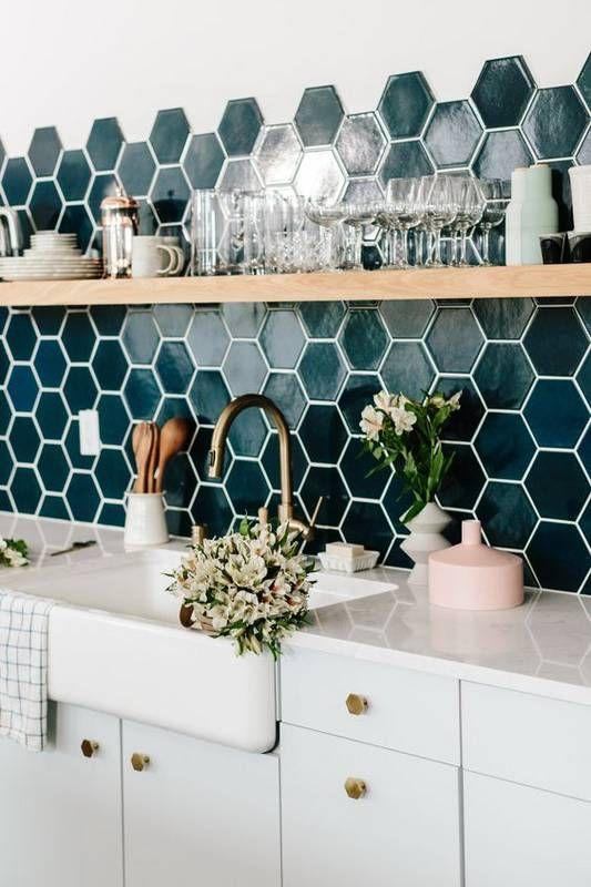 white sink with white cabinet under, green hexagonal tiles backsplash, wooden board shelf
