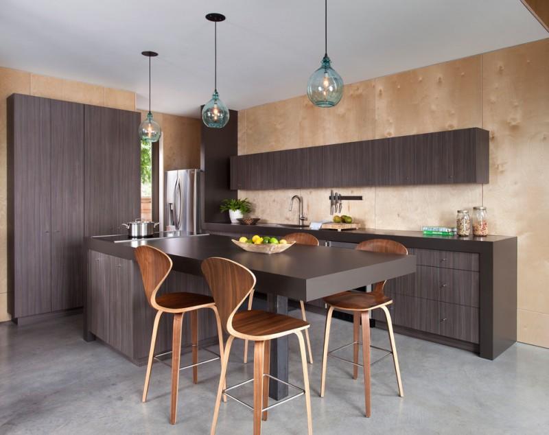 wood stool blue glass pendnat lights dark brown wooden cabinets beige walls dark brown countertop island sink stovetop grey floor