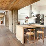 Wood Stool Grey Island Grey Flat Panel Kitchen Cabinets Built In Appliances Grey Countertop Pendant Lamps Range Hood Stovetop Sink Glass Window