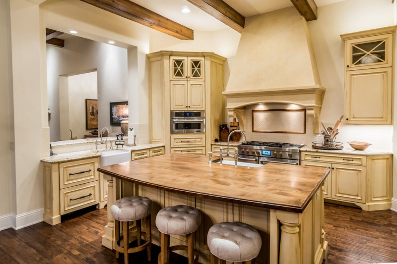 wood stool tufted stool cushion beige island yellow kitchen cabinets stovetop oven granite countertops range hood backsplash white sink