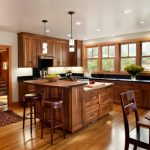 Wood Stool Wooden Kitchen Cabinets Wooden Island Wooden And Black Countertops Patterned Kitchen Mat Wooden Dining Table Pendant Lamps Window Stove Range Hood Sink