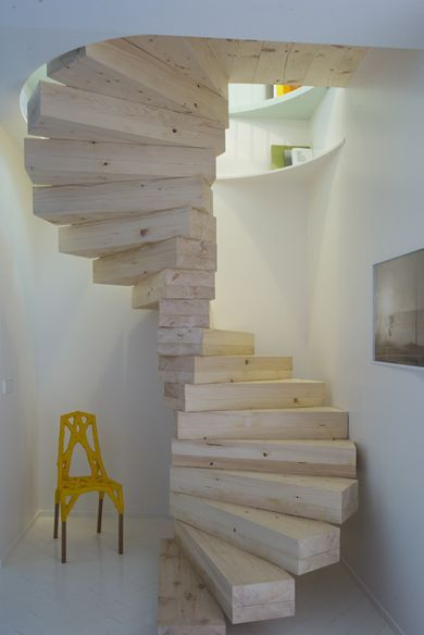 wooden blcok stairs circled in small space with white wall, yellow chair
