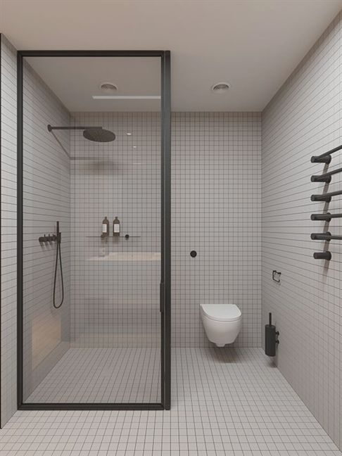 bathroom with small white square tiles on the walls and floors, white toilet, shower area parted with glass
