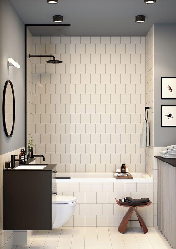 bathroom with white square tiles on the walls, floor, white bath tub, white toilet, wooden stool, dark brown sink with round mirror