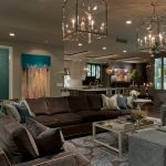 Brown Suede Sectional Couch Chandelier Glass Coffee Table Patterned Rug Grey Armchair Grey Stools Mirror Cabinet Colorful Artwork