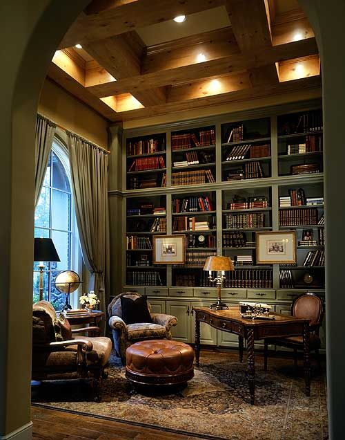 classic home library with green wooden bookcase, brown rug, chairs, ottoman, curtain