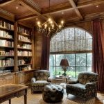 Classic Home Library With Wooden Floor, Wooden Ceiling, Old Dark Brown Wooden Bookcase, Chandelier, Chairs, Ottoman, Tables, Table Lamp