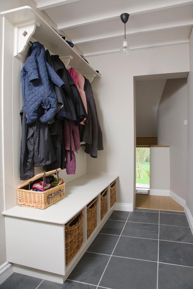 coat rack wall mount grey floor tiles whitet wooden bench rattan baskets grey walls ceiling lamp ceiling beams bench cubbies