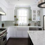 Fireclay Farm Sink White Framed Glass Window Grey Subway Tile Wooden Floor White Cabinets Dishwasher Stovetop Rangehood Marble Countertop