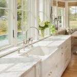 Fireclay Farm Sink White Framed Glass Window White Marble Countertops Dishwasher White Cabinets Chrome Faucet Wooden Floor