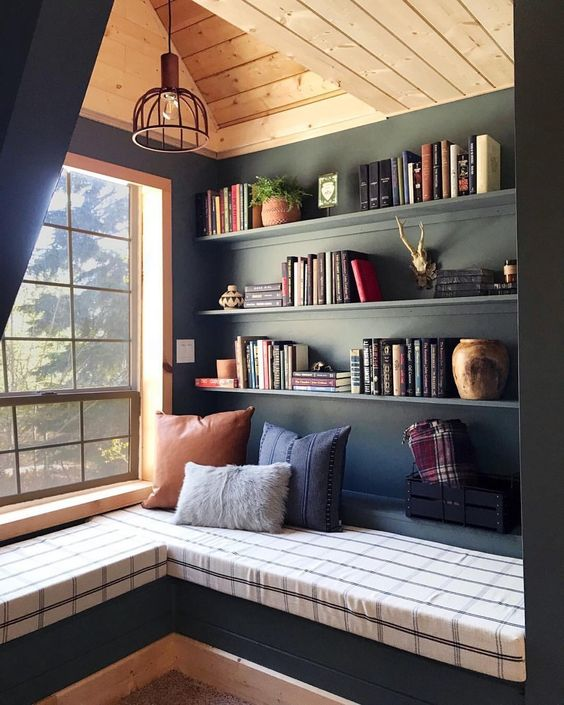 home library in the corner with black shelves, lamp, bench with plaid cushion