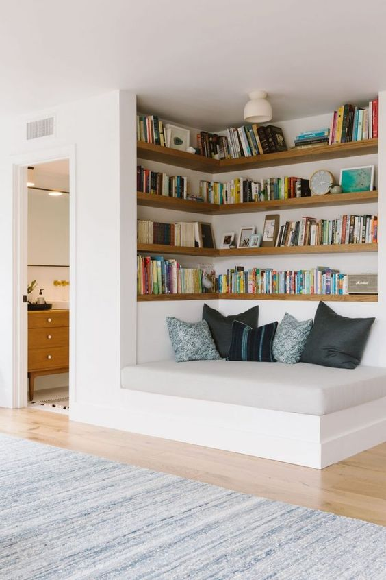 home library with brown wooden shelves, grey bed, pillows