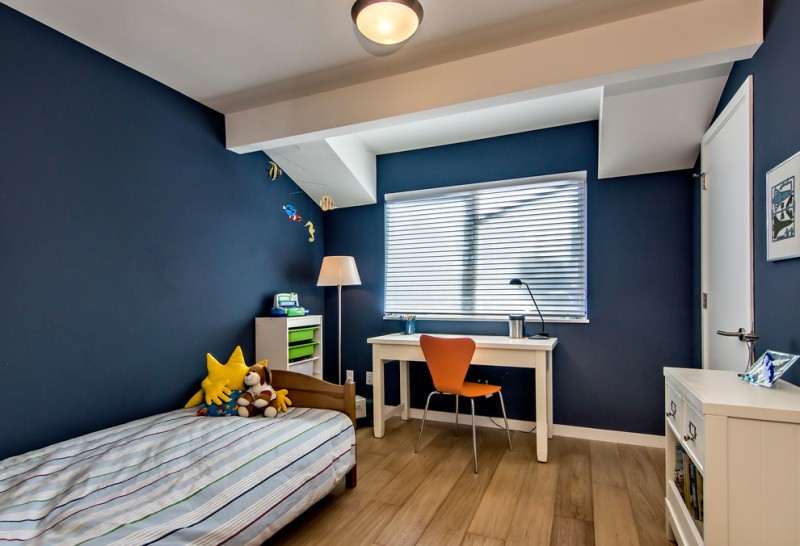kids bedroom desk blue walls window blind floor lamp wooden bed white desk orange chair wooden floor white storage ceiling lamp striped bed cover