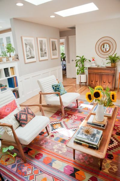 living room with beige wal, white cushioned wooden chair, wooden coffee table, colourful rug