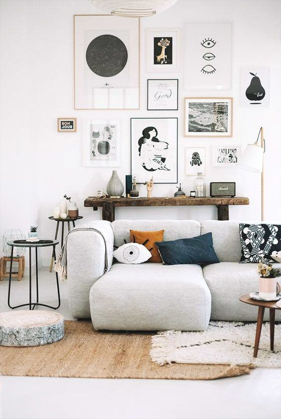 living room with grey sofa, white wall, white floor, brown rug, white rug, small round coffee table