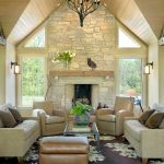 Living Room With Recliners Brown Leatherd Stool Fireplace Wood Mantel Grey Sofas Throw Pillows Floor Lamp Wall Sconces Window Floral Area Rug Glass Coffee Table
