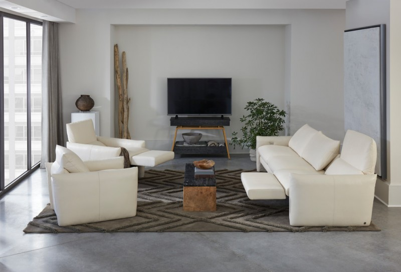 living room with recliners coffee table brown textured area rug white leathered sofa armchairs indoor plant grey floor glass window grey curtain