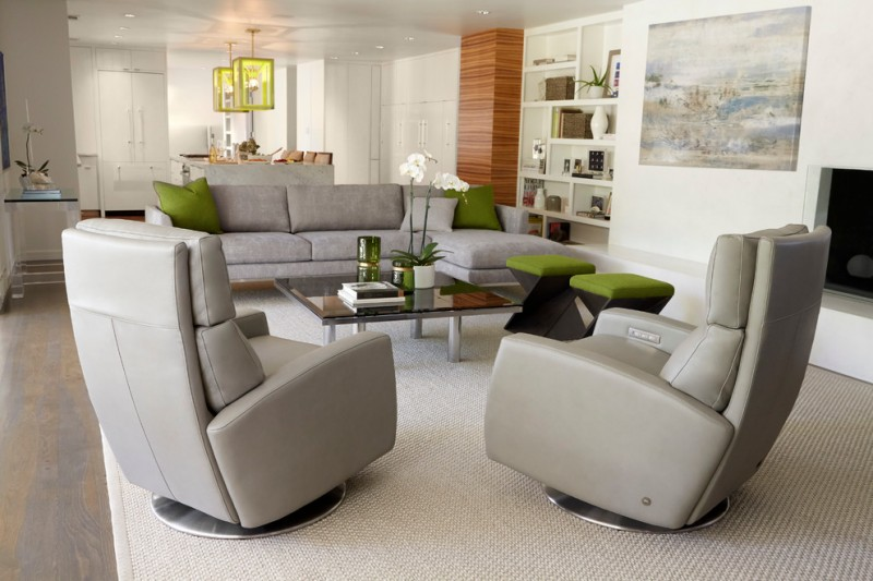 living room with recliners grey couch green stools green pillows glass coffee table white shelves beige area rug orchid artwork