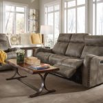 Living Room With Recliners Grey Sofa Armchair Wooden Coffee Table Glass Table Lamp Window Seat Throw Pillows Brown Area Rug Glass Windows Artwork