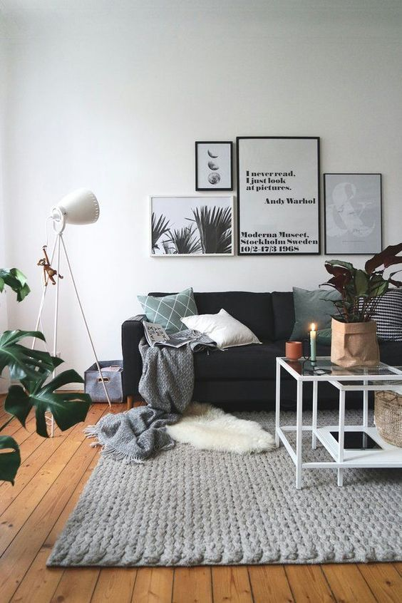 living room with white wall, wooden floor, black sofa, coffee table