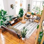 Living Room With White Wall, Wooden Floor, Brown Leather Sofa And Chairs, Orange Ottoman, Plants, White Rug