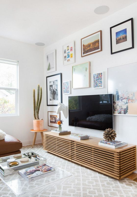 living room with white walls, tv, wooden cabinet, grey patterned rug